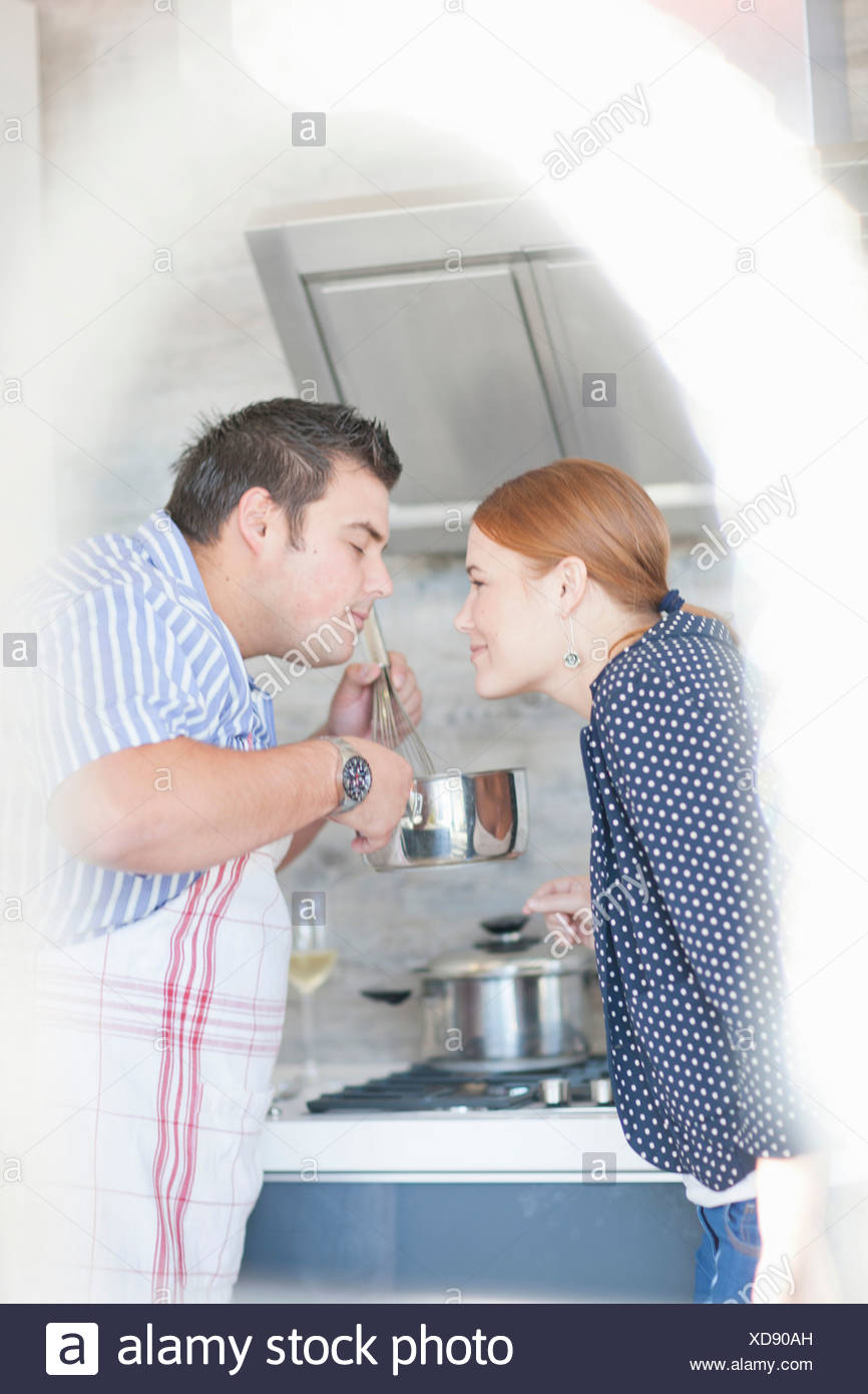 Young couple smelling cooking aroma from saucepan - Stock Image