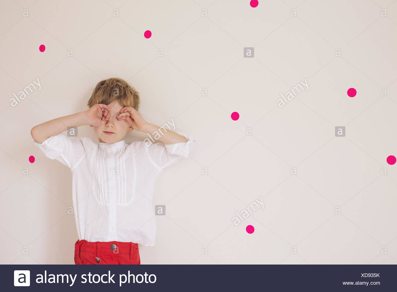 Little boy covering eyes with his hands, portrait - Stock Image