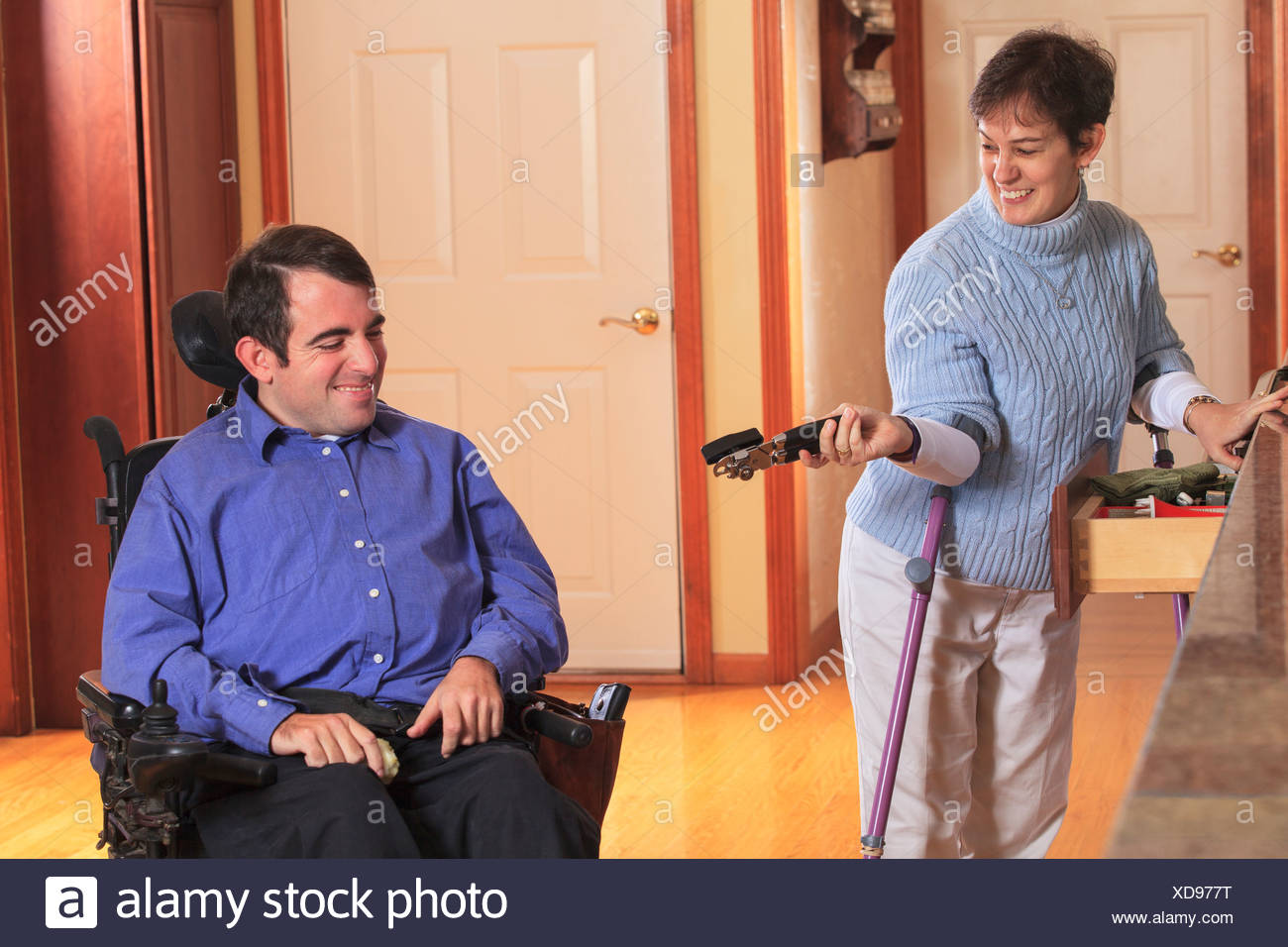 Woman with Cerebral Palsy using crutches and giving a can opener to her husband in a wheelchair with Cerebral Palsy - Stock Image