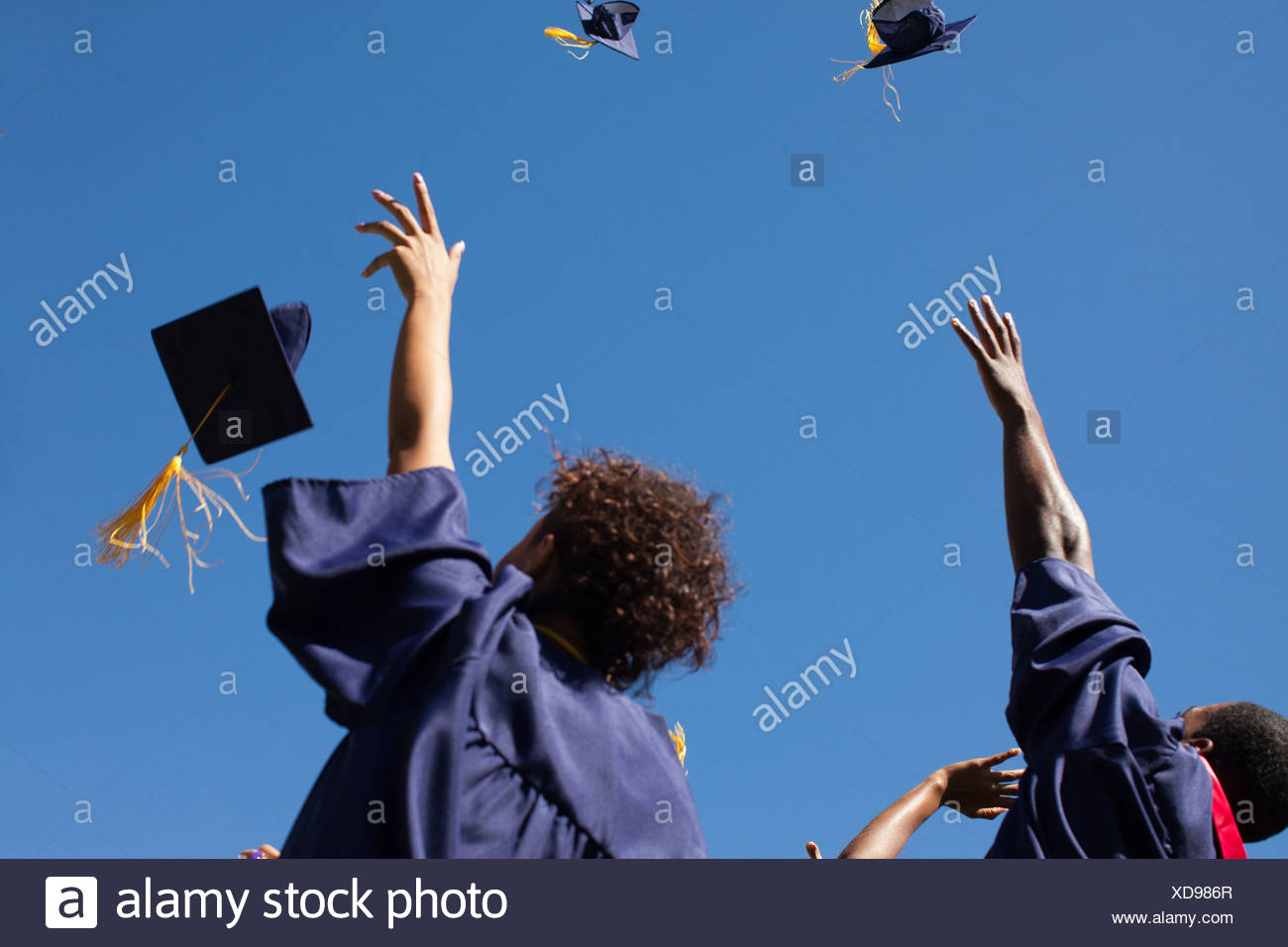 Graduates throwing caps in air outdoors Stock Photo