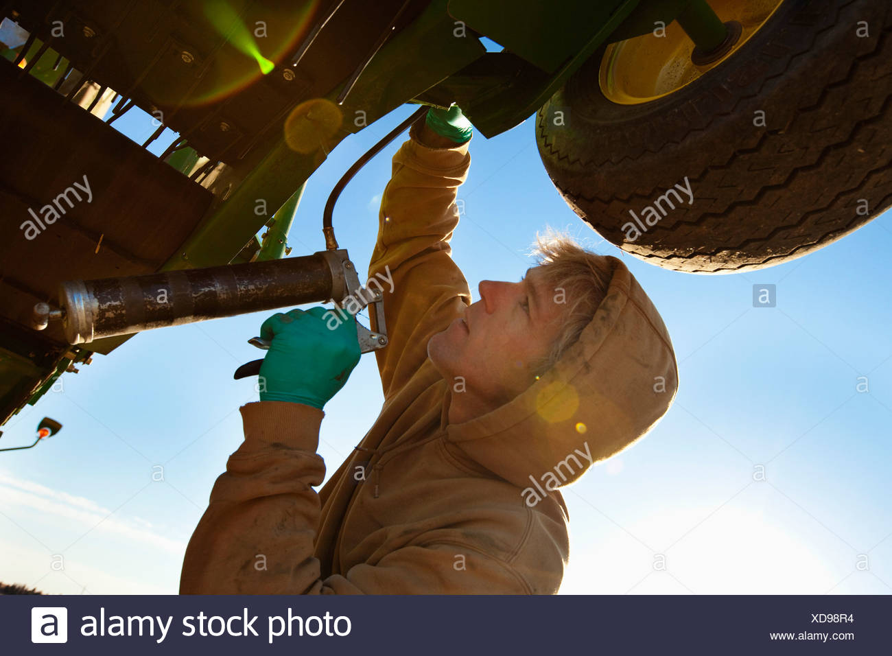 A Person Works On Farm Equipment; Three Hills, Alberta, Canada Stock Photo