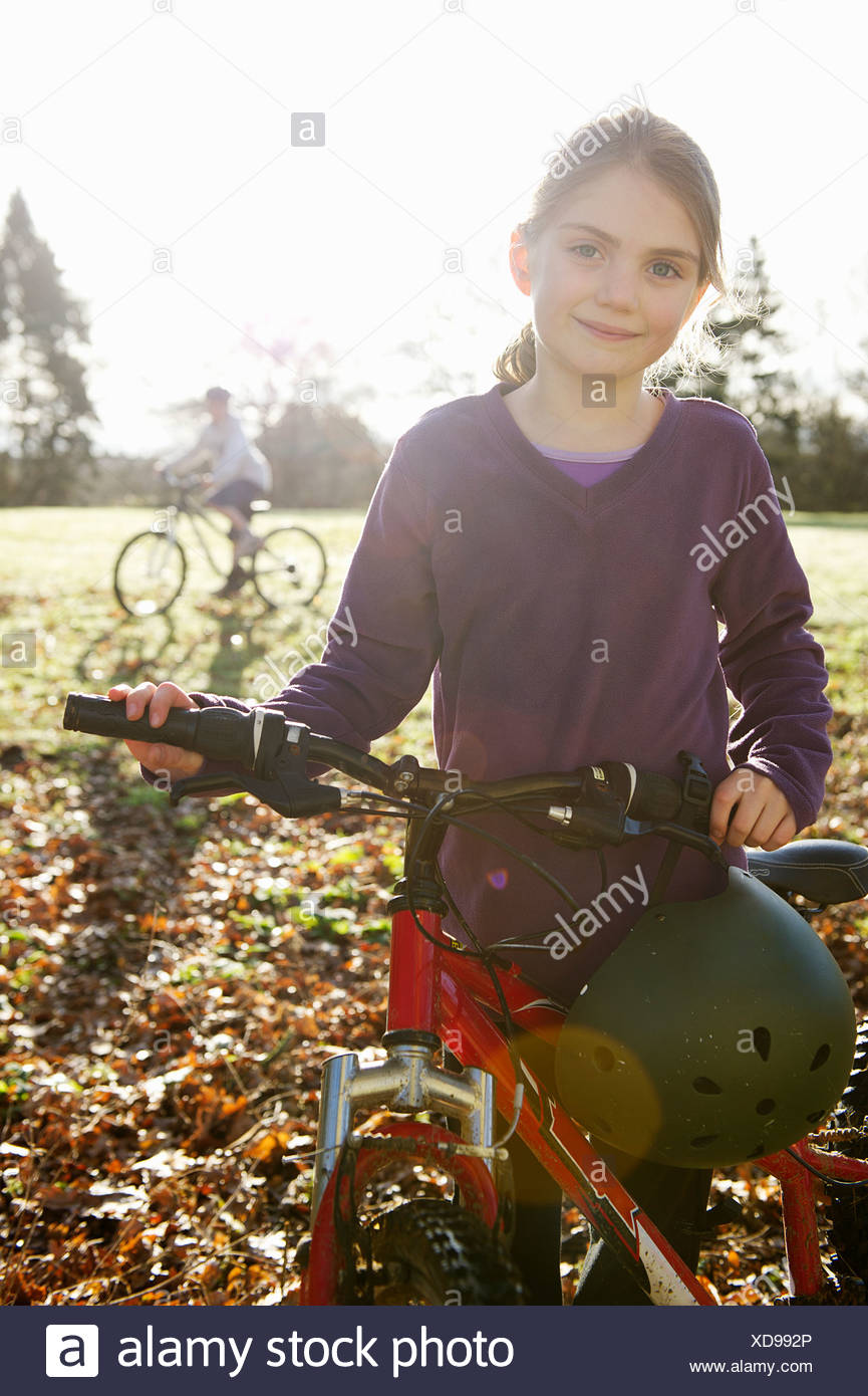 Girl walking bicycle in meadow - Stock Image