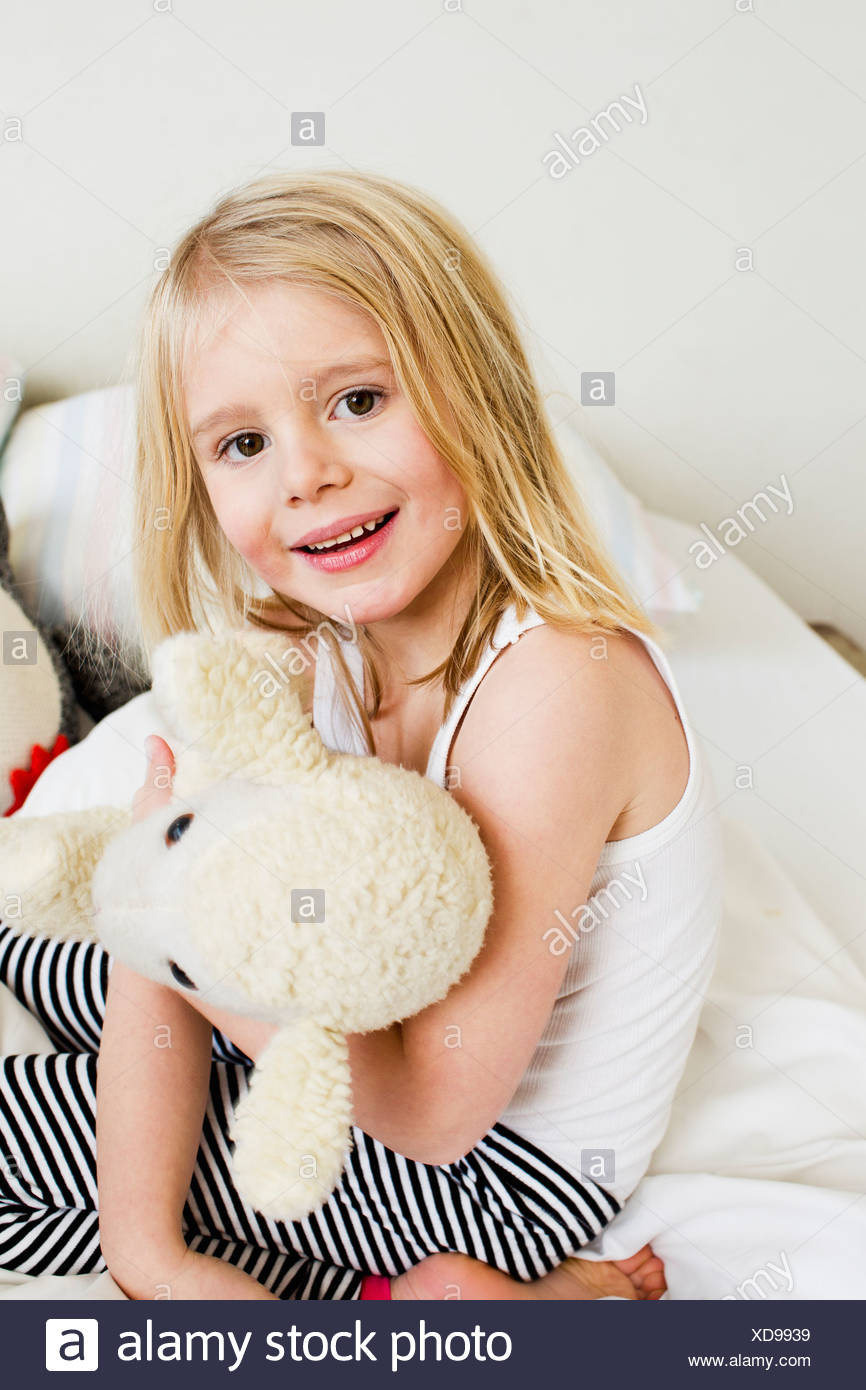 Portrait of young girl kneeling on bed with soft toy - Stock Image