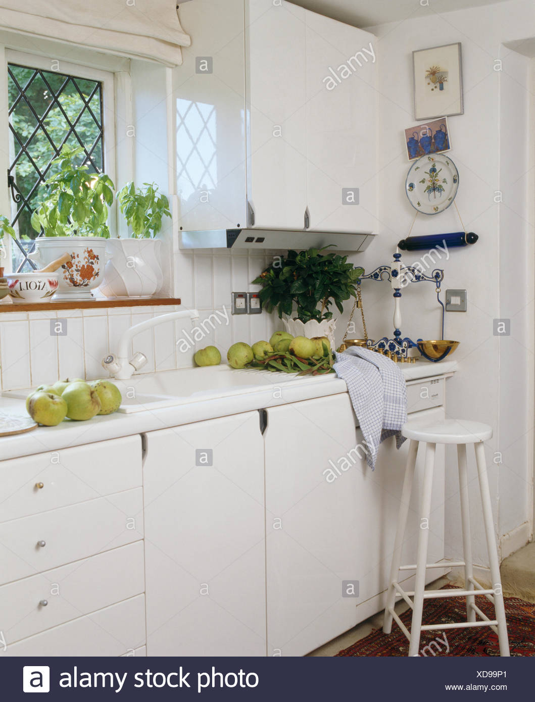 White stool beside sink in small, white cottage kitchen ...