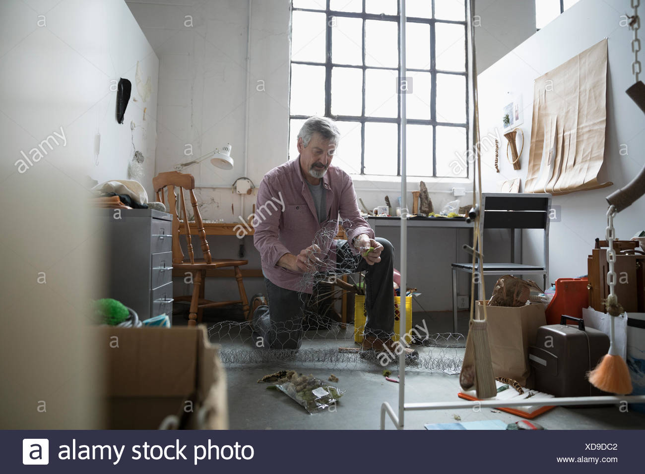 Male artist forming wire in art studio - Stock Image