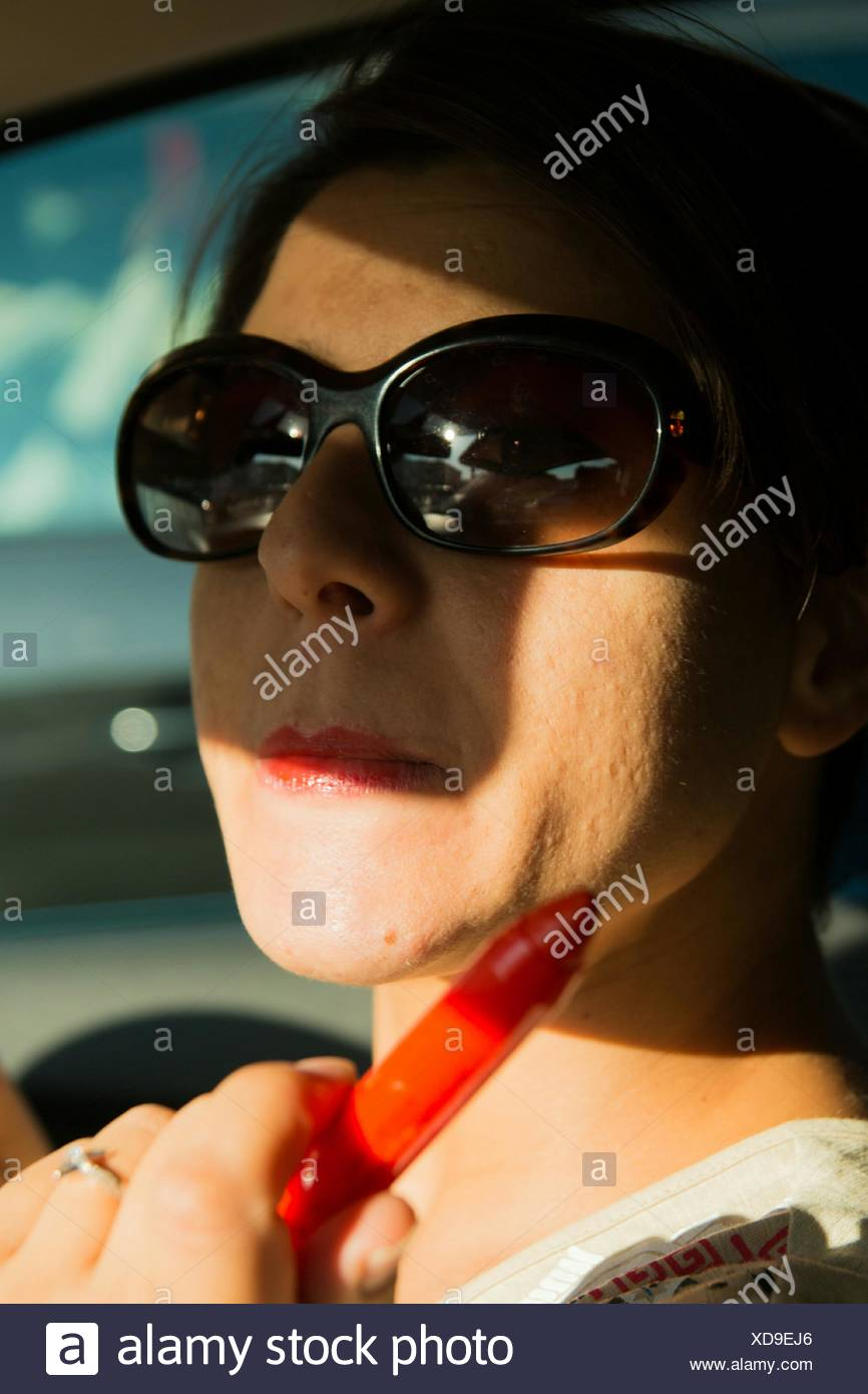 Young Woman Wearing Sunglasses Holding Red Lipstick While Sitting In Car Stock Photo