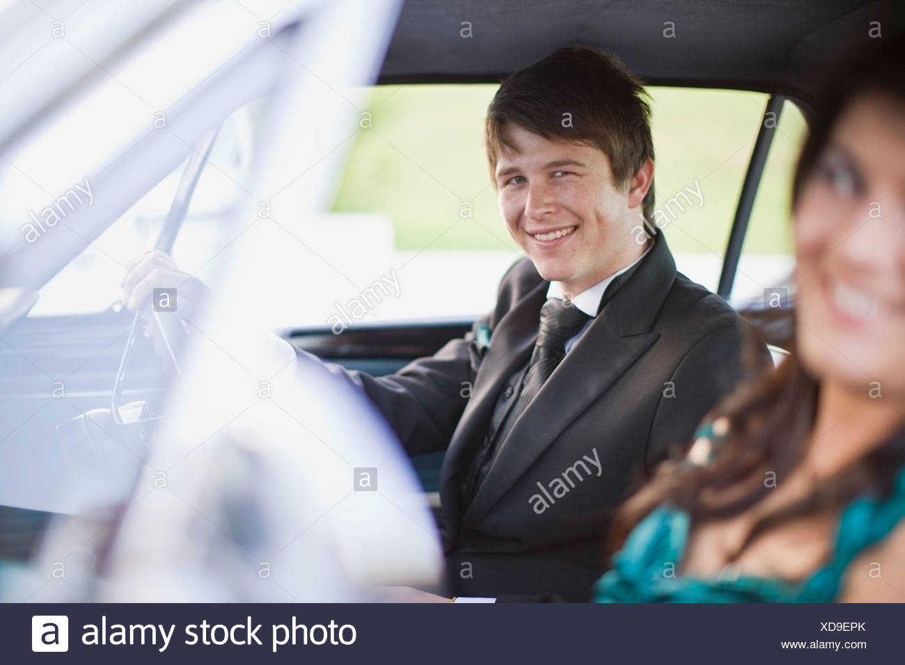 Teenagers driving car in formal wear - Stock Image