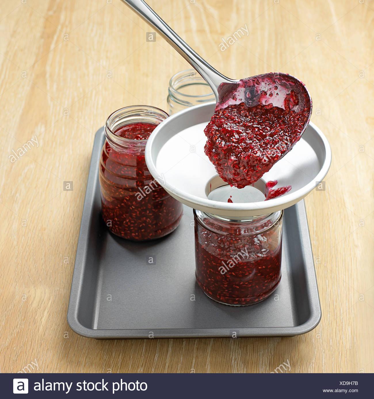 Putting jam into jars through funnel, close-up - Stock Image