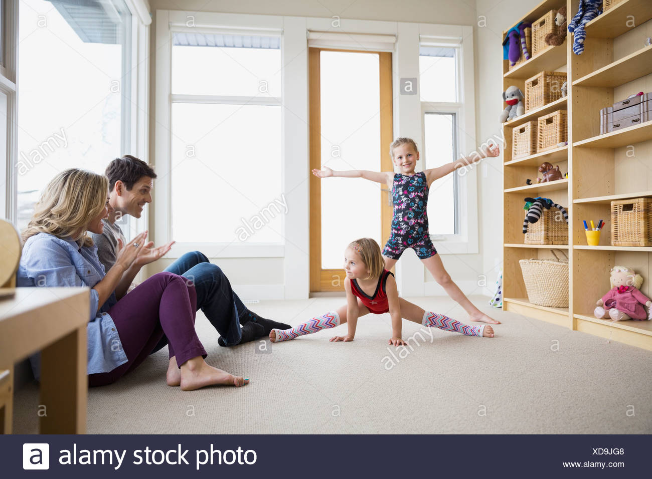 Parents watching daughters dance in living room - Stock Image