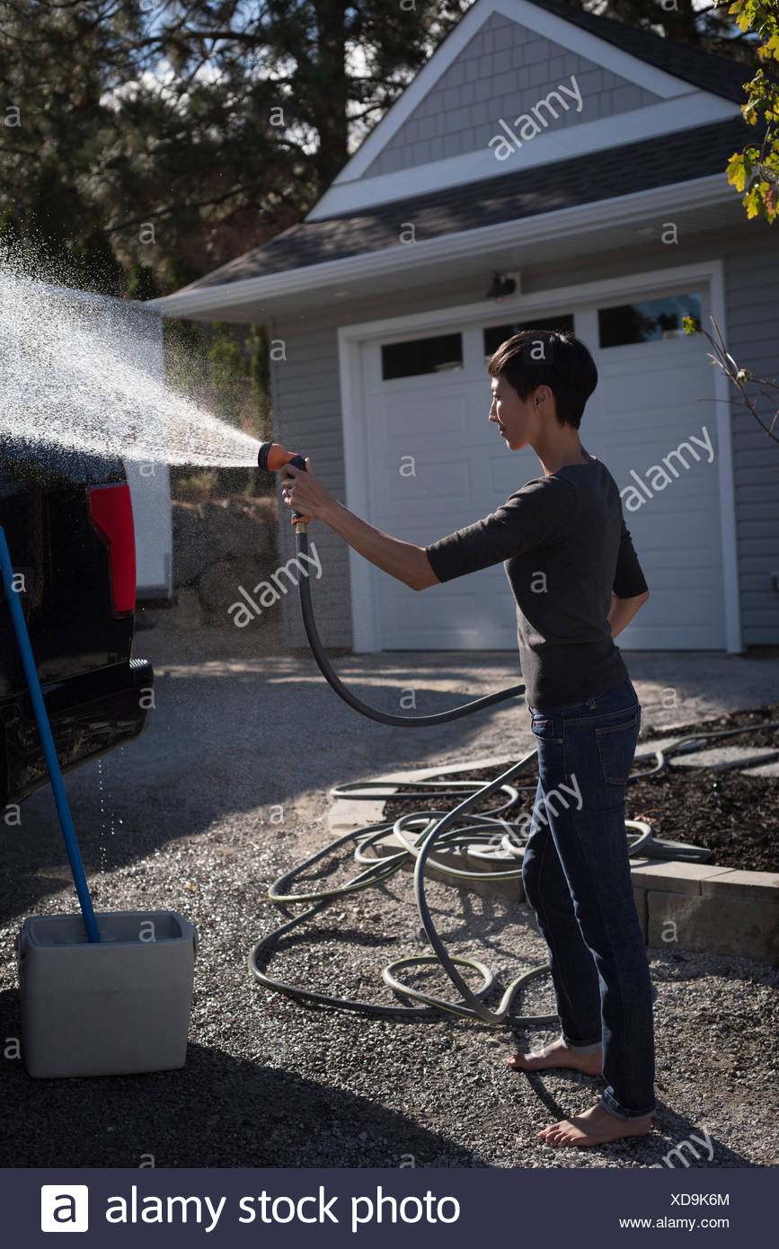Woman washing her car with a high pressure water jet - Stock Image