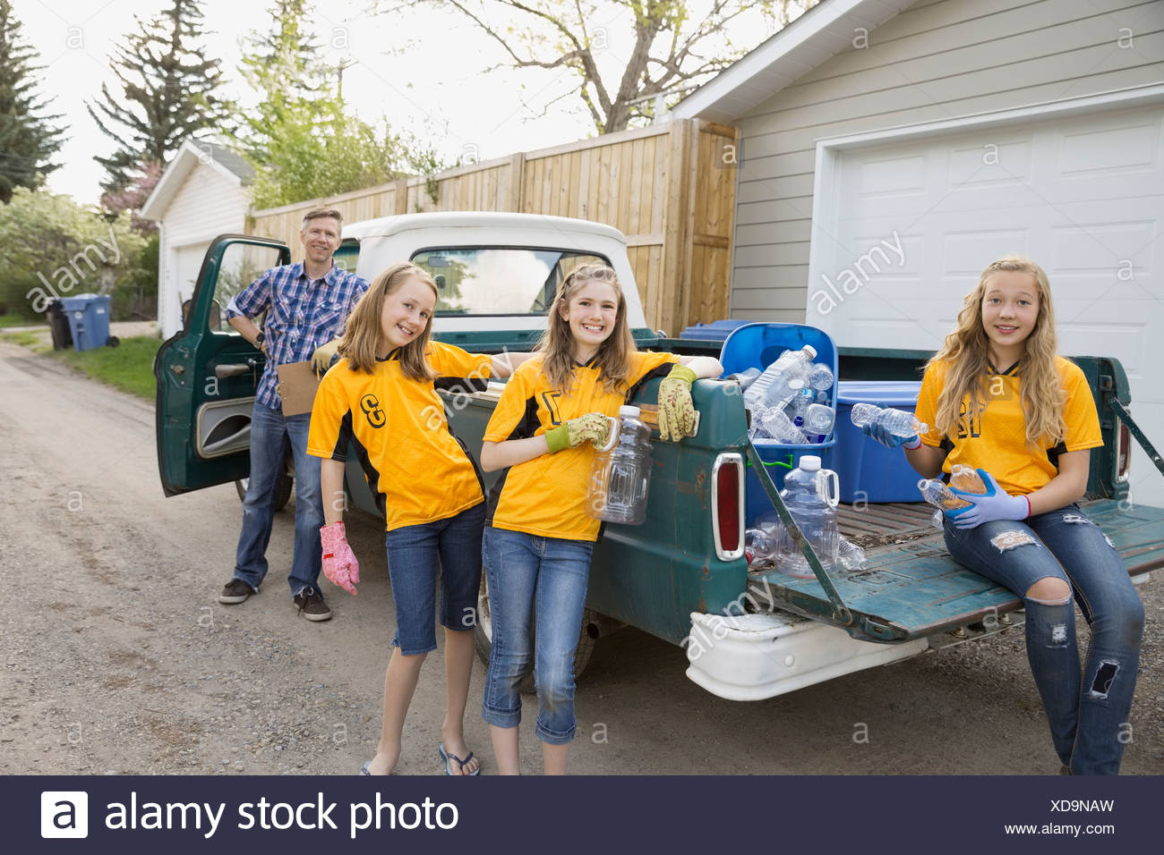 Portrait of father and daughters with recycling bins - Stock Image