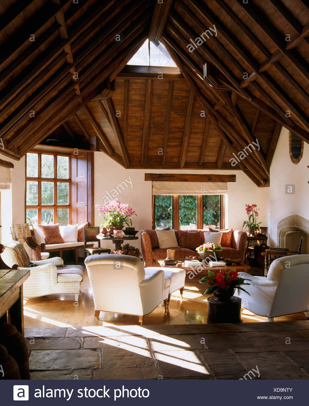 High, vaulted beamed roof in large barn conversion sitting room with white armchairs and sofa and flagstone and wooden floor - Stock Image