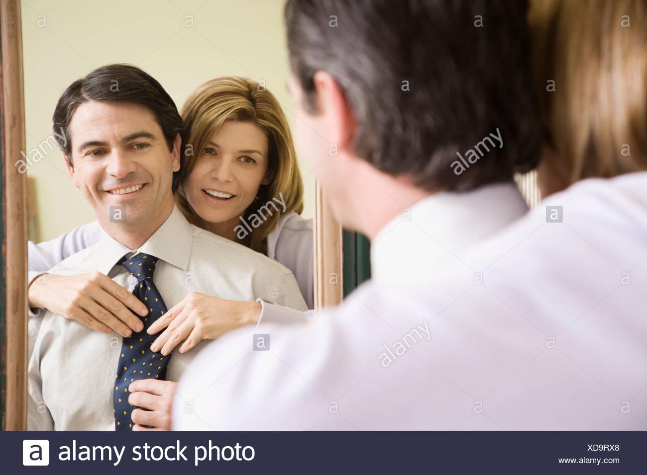 Woman adjusting husband's necktie - Stock Image
