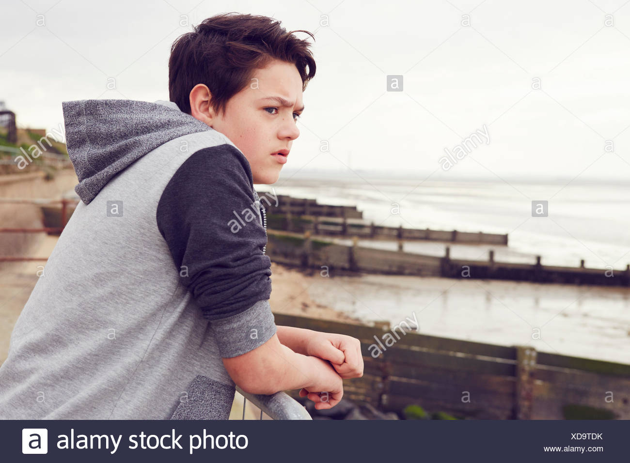 Unhappy teenage boy looking out from railings, Southend on Sea, Essex, UK - Stock Image