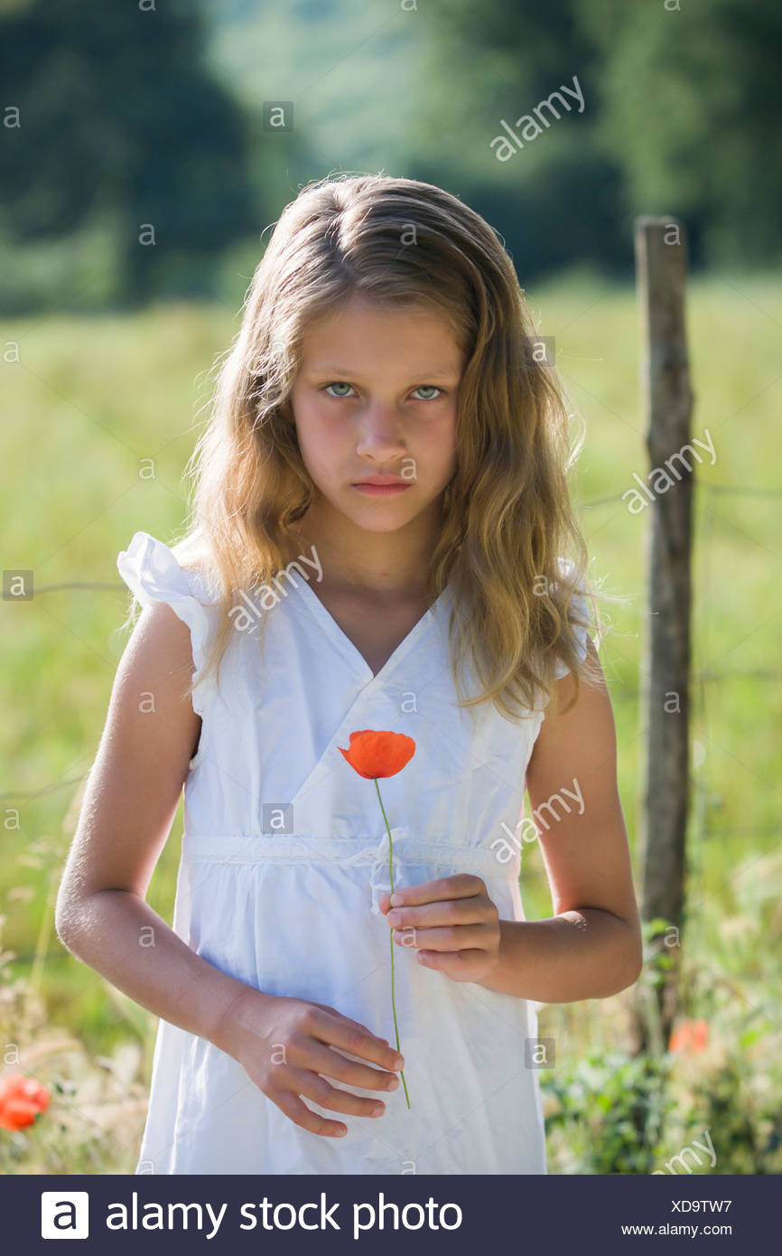 Portrait of little girl with poppy in her hand - Stock Image