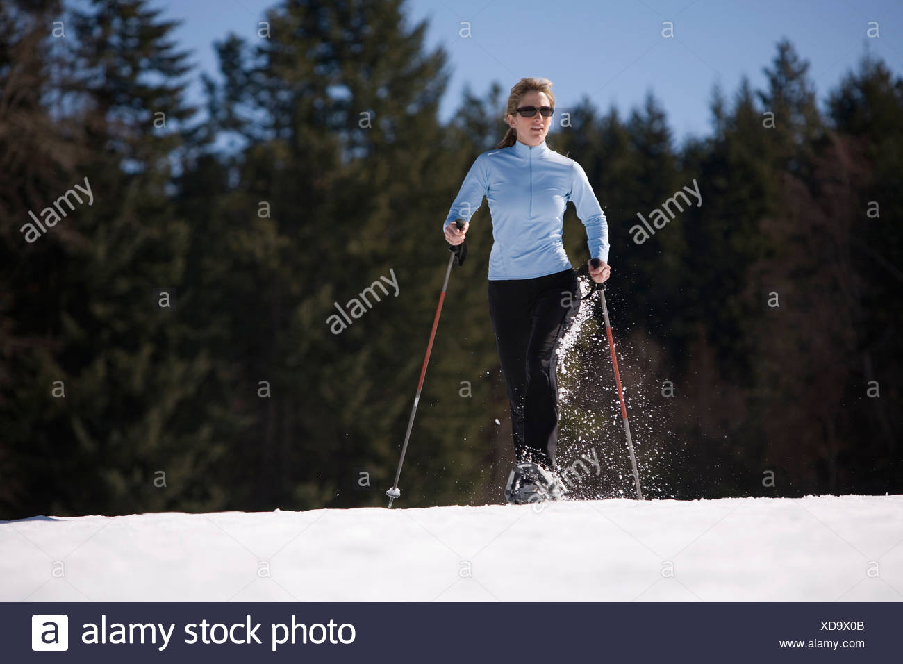 Young woman runs through snow with snowshoes near Mt. Hood, Oregon. - Stock Image