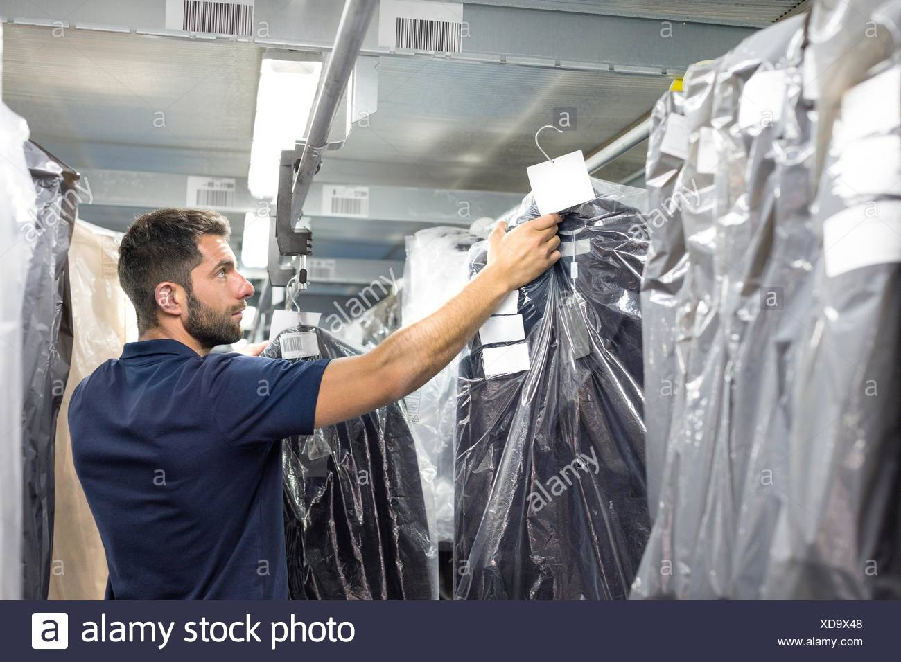 Male warehouse worker stock taking in distribution warehouse - Stock Image
