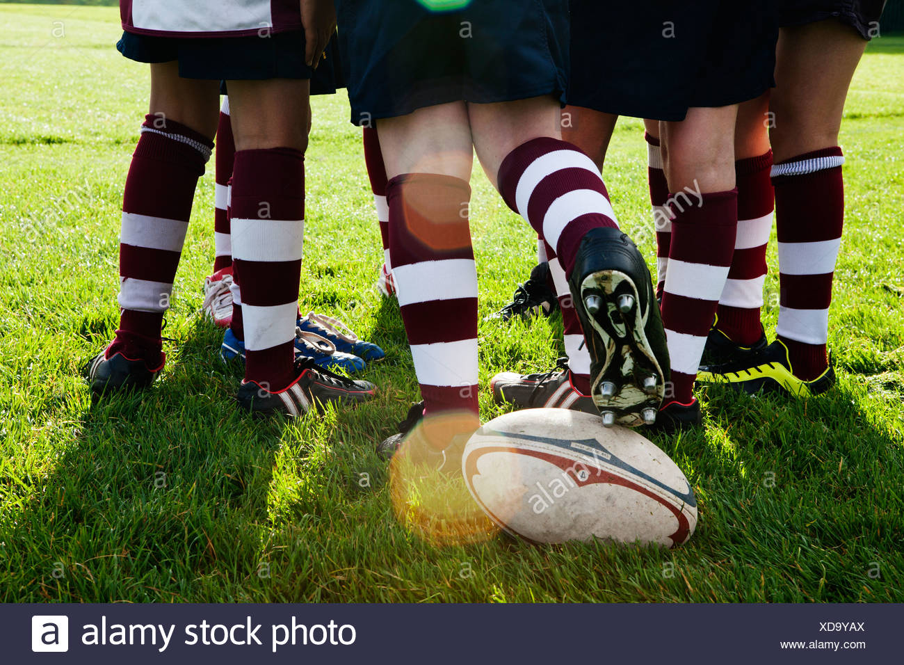 Teenage schoolboy rugby team kicking ball from huddle - Stock Image