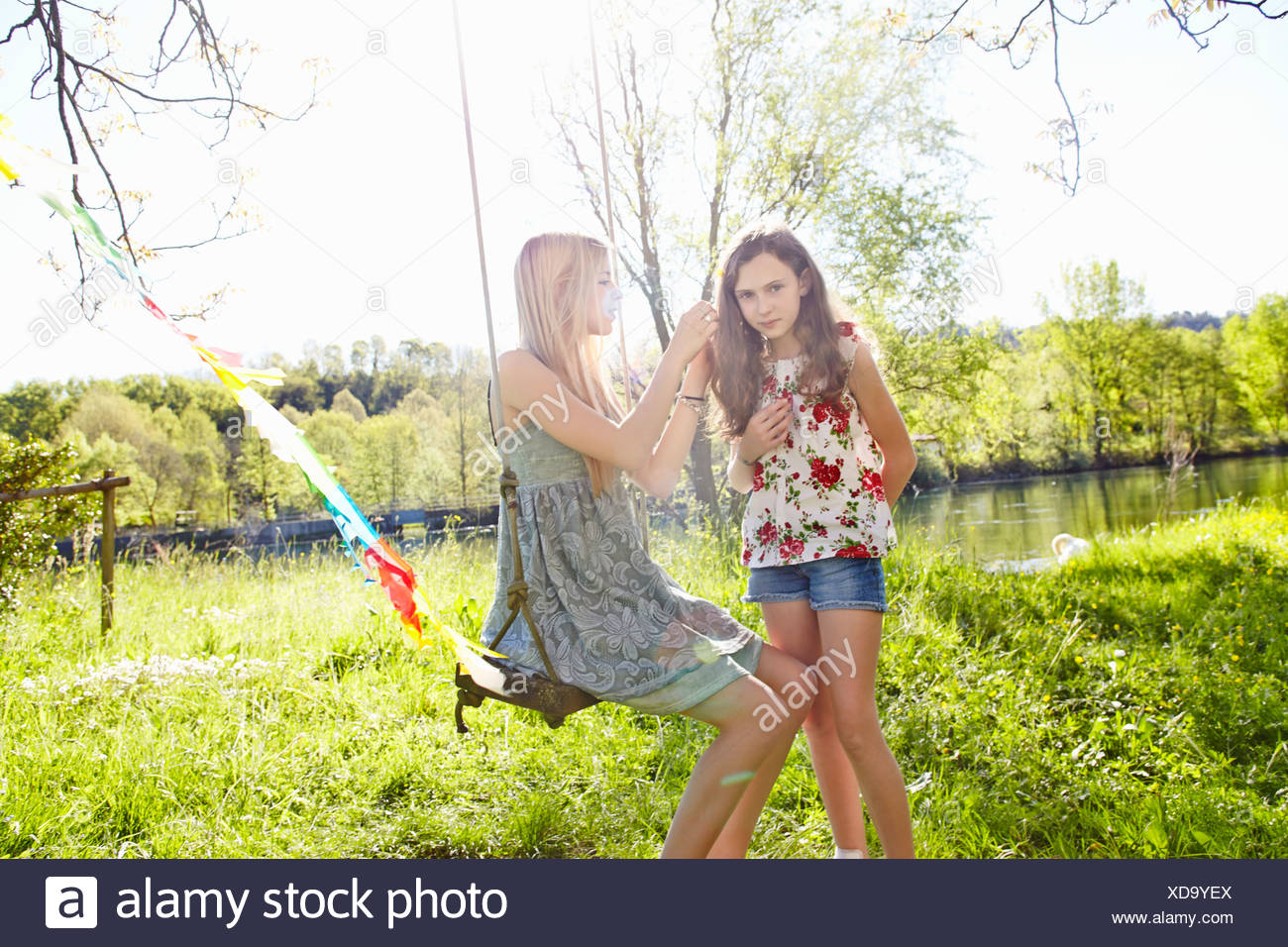 Young woman on swing with friend - Stock Image