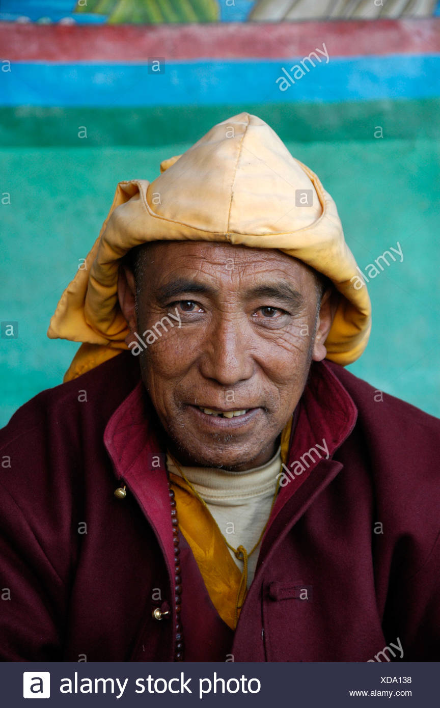 Buddhist monk lama wearing a yellow cap of Sakya-pa sect in the old monastery gompa of Dzong Mustang Annapurna Region Nepal - Stock Image
