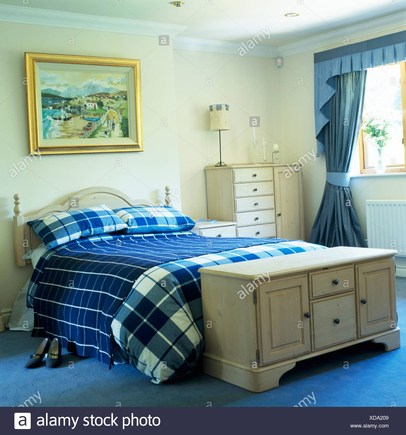 Pale wood chest below bed with blue checked bed-cover and ...