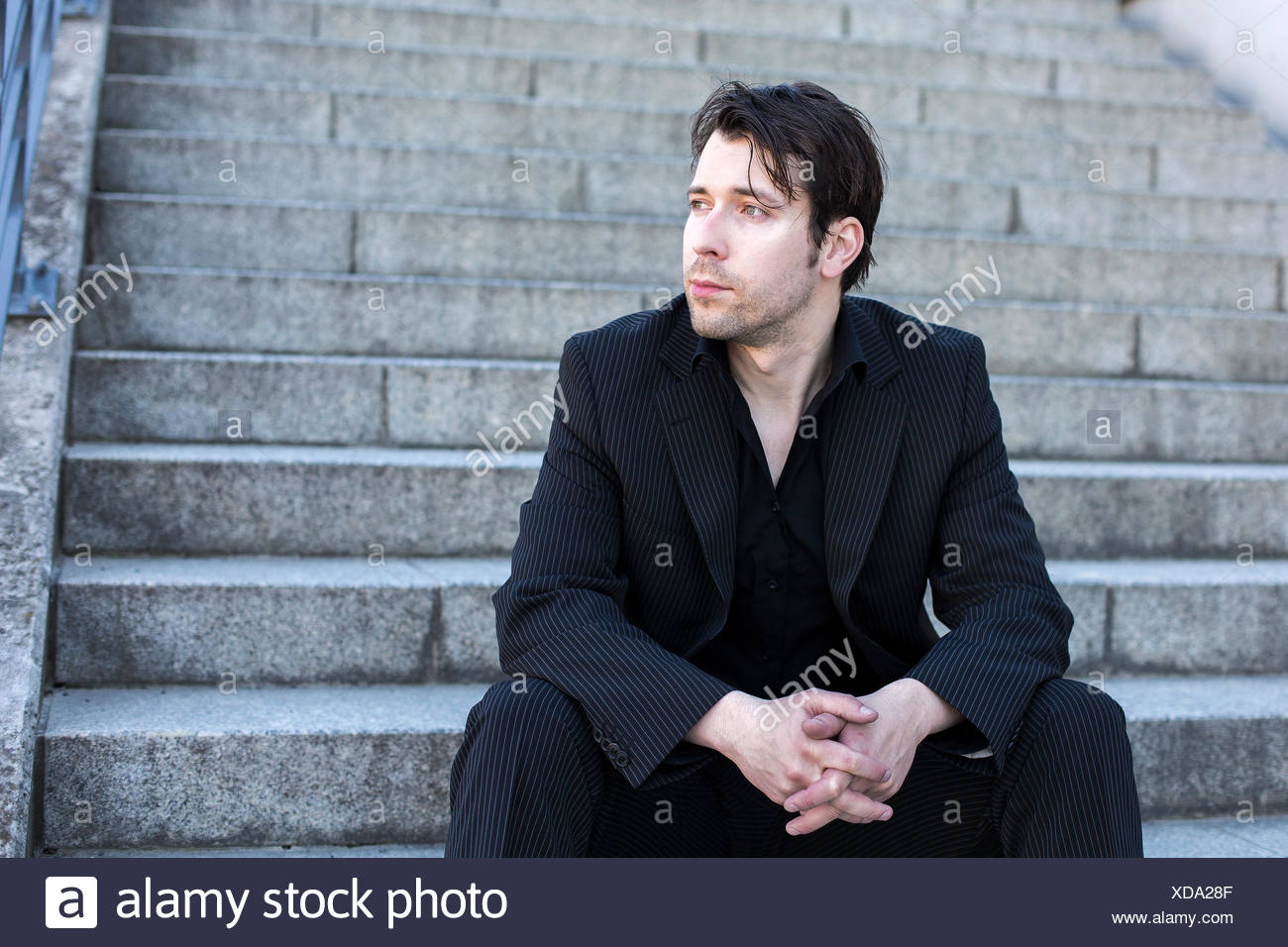 businessman sitting on stairs - Stock Image