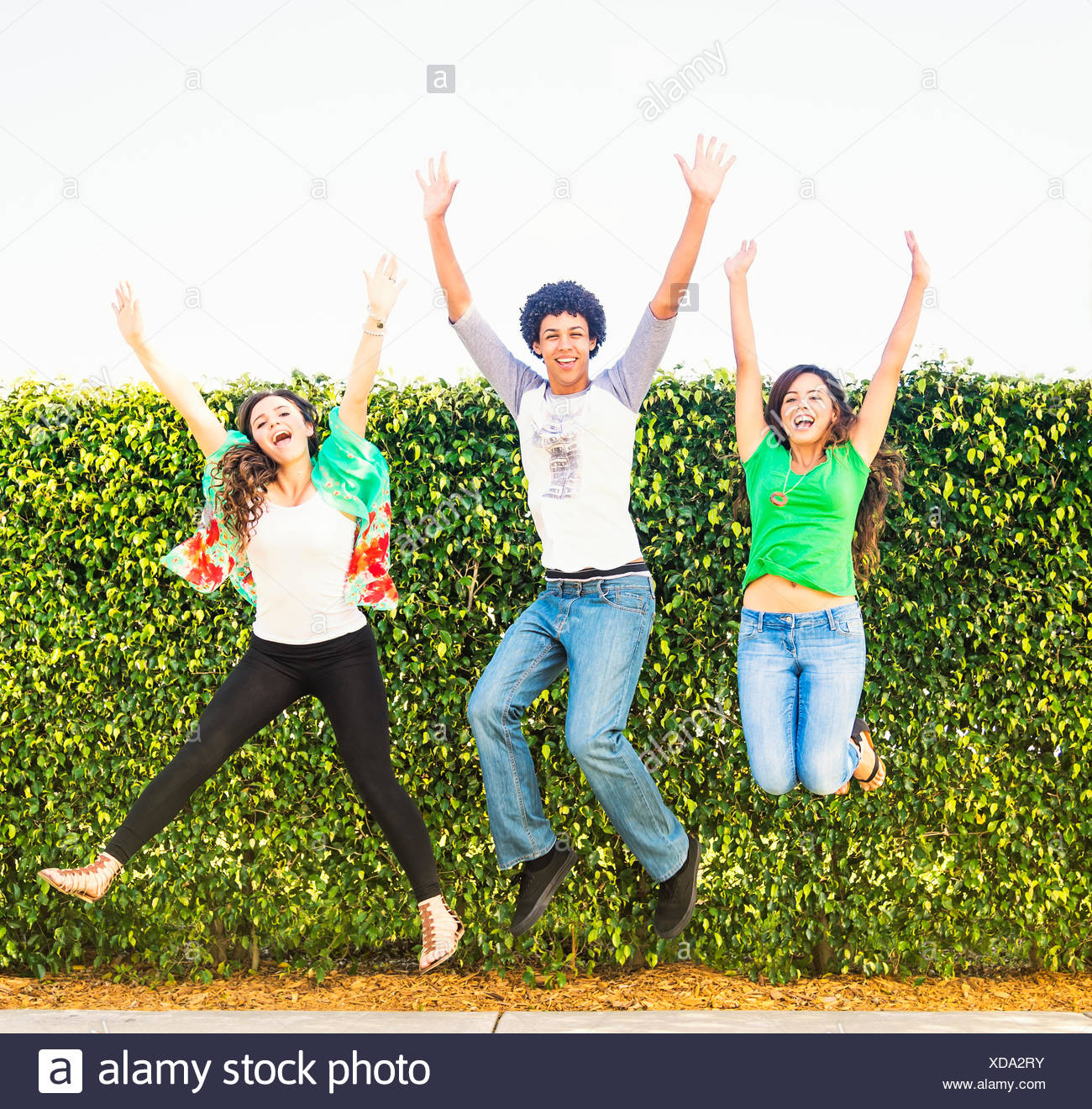 Portrait of friends (14-15) jumping - Stock Image