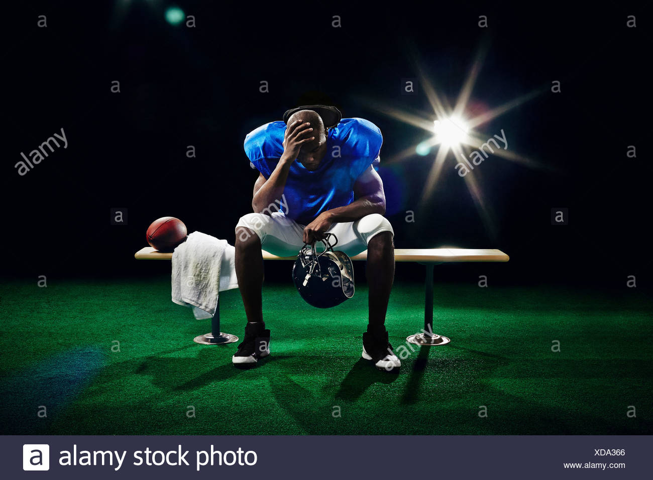 Portrait of american football player with head in hand - Stock Image