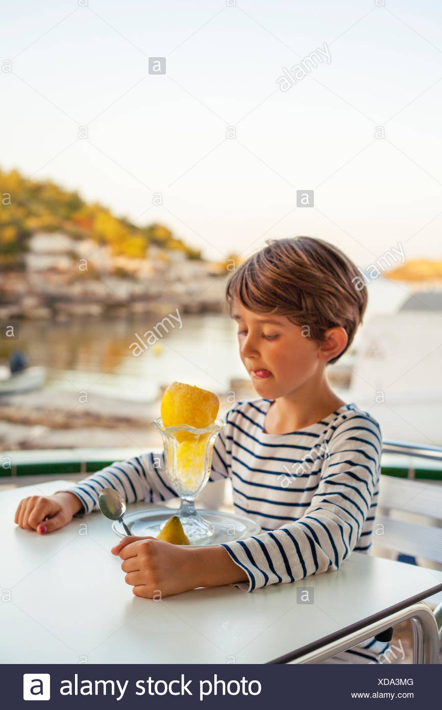 Spain, Menorca, Boy (6-7) licking lips while looking at orange - Stock Image