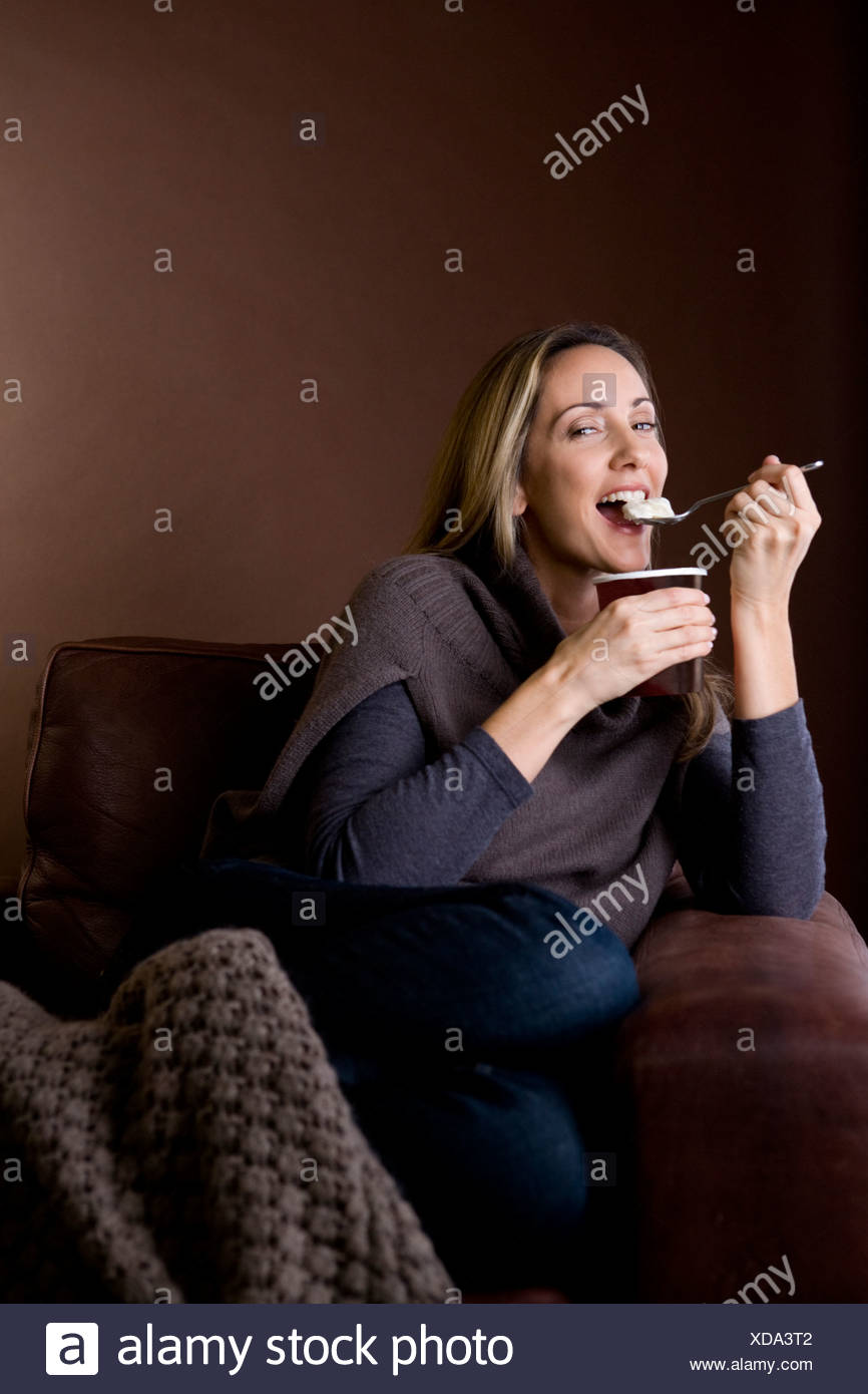 A mid adult woman eating ice cream - Stock Image