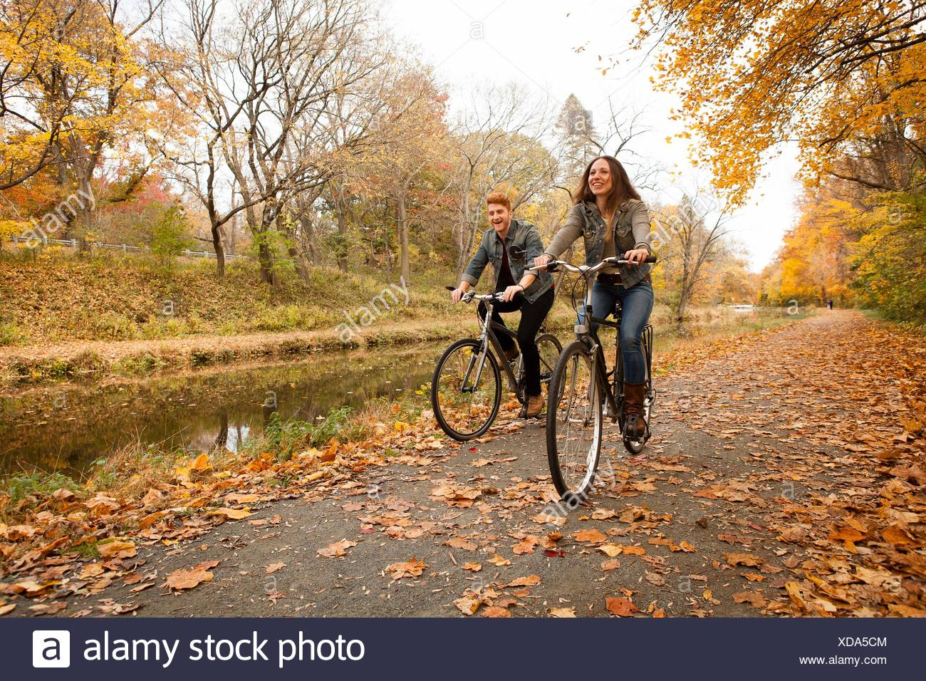Happy young couple cycling along riverside in autumn - Stock Image