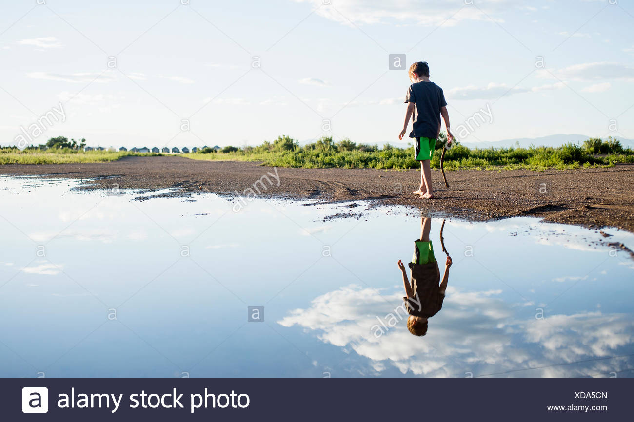 Boy (6-7) walking on lake shore - Stock Image