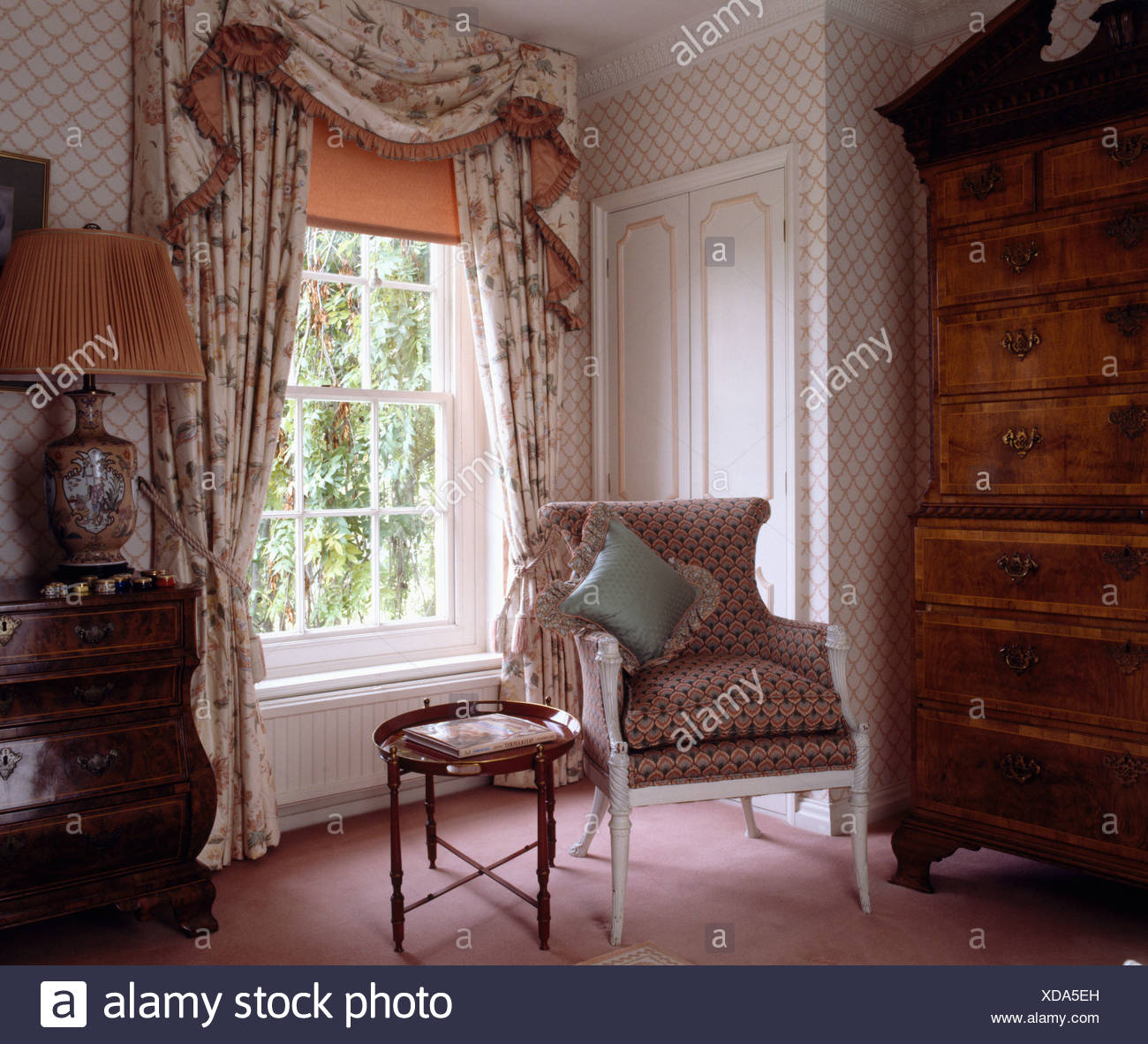 Orange blind and floral swagged curtains in bedroom with small table ...
