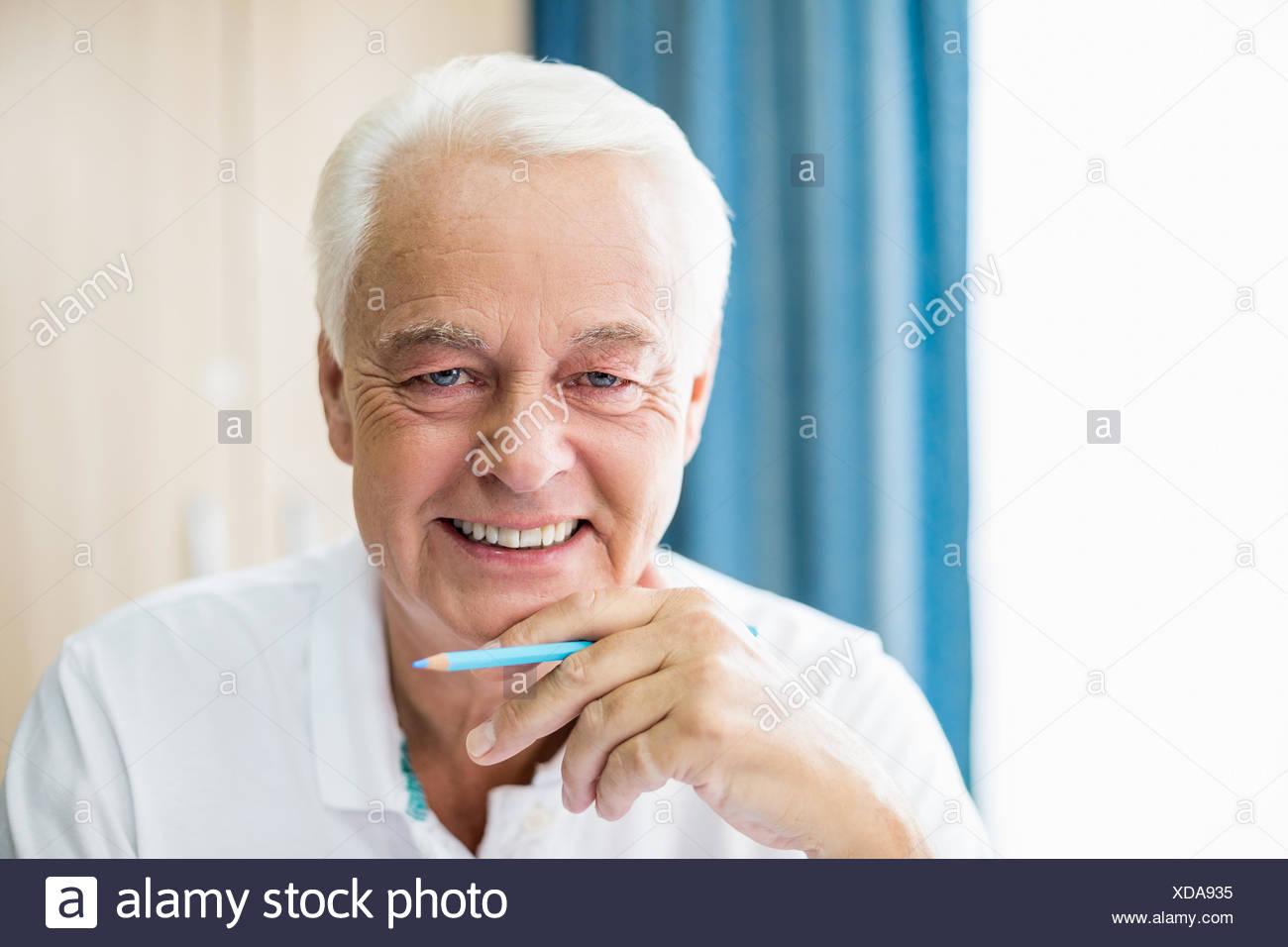 Smiling senior holding coloured pencil - Stock Image