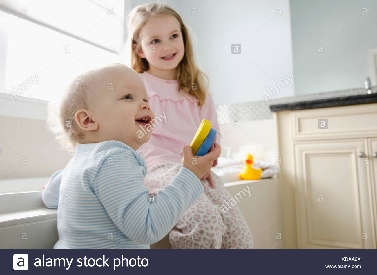 young girl with younger brother in bathroom - Stock Image
