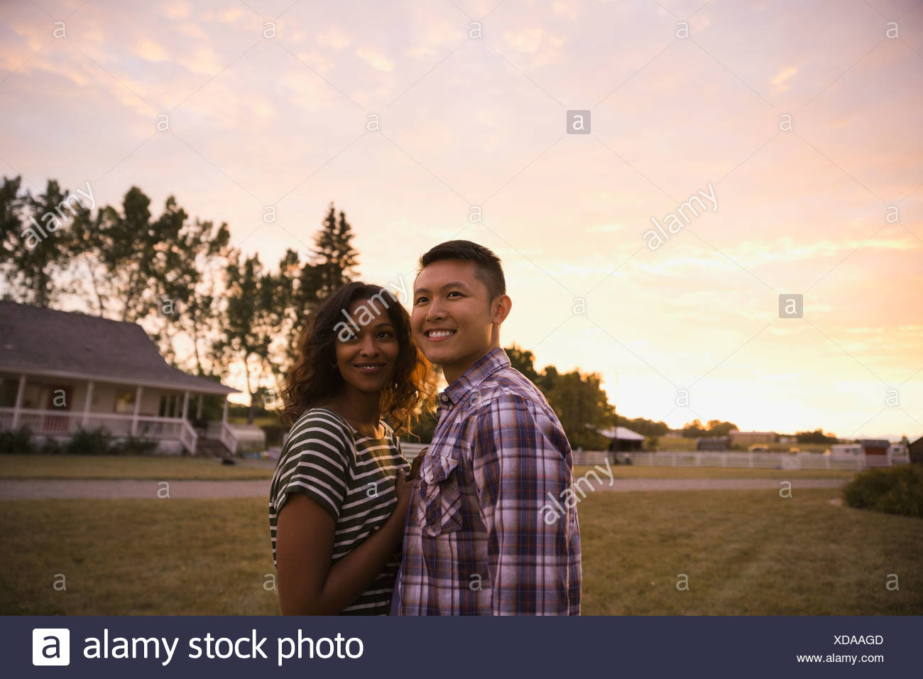 Portrait of multi-ethnic couple standing outdoors - Stock Image