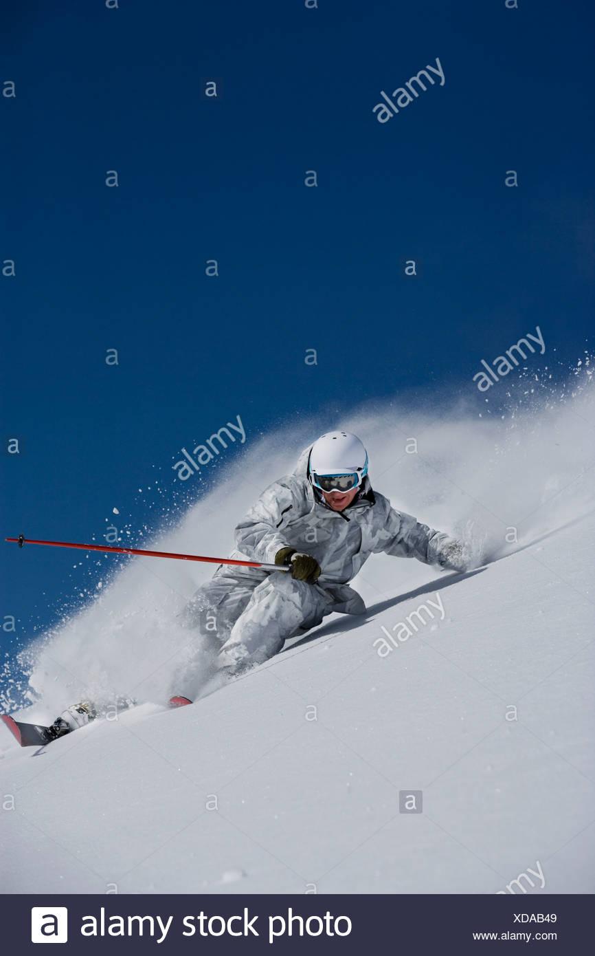 Man in white & grey suit powder-turn. - Stock Image