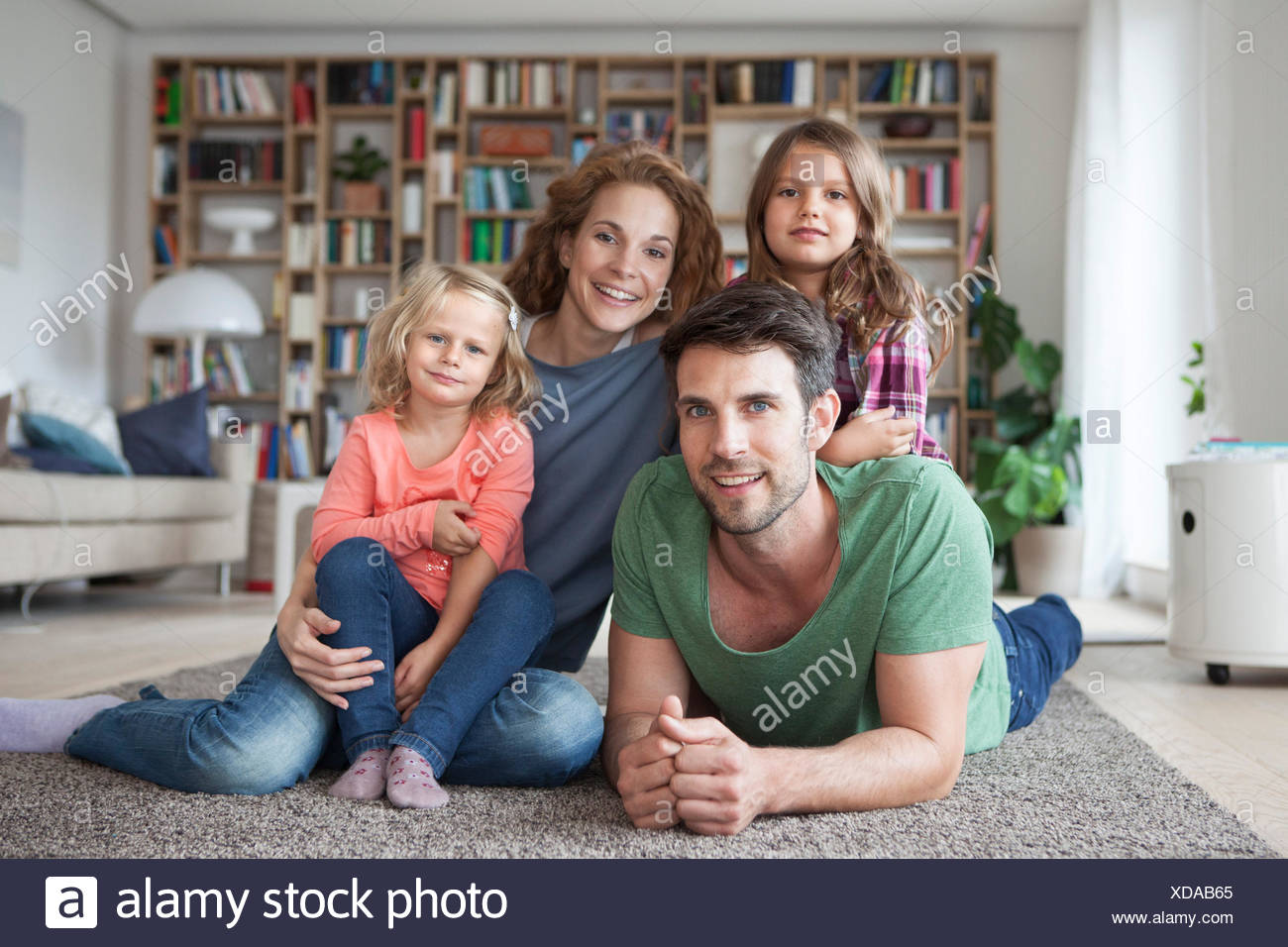 Family portrait of family with two little girls on the floor of living room - Stock Image