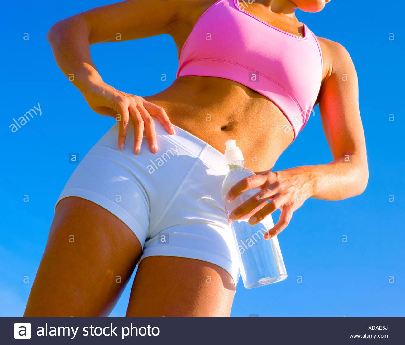 Athletic woman working out in a meadow, from a complete series of photos. - Stock Image