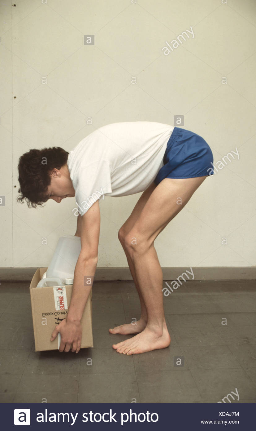 teenager demonstrating poor posture while picking up a heavy object - Stock Image