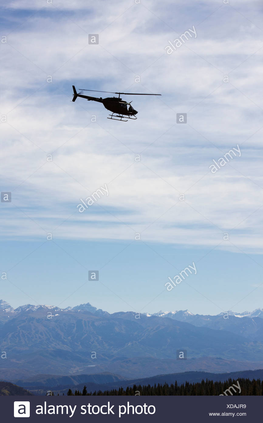 Silhouette of a U.S. Army National Guard OH-58 Kiowa above Colorado's Rocky Mountains. - Stock Image