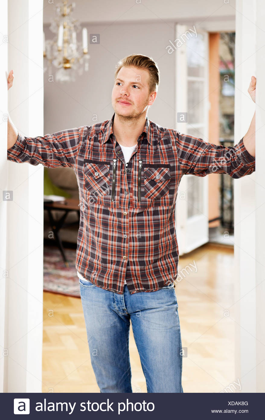 Mid adult man in checked shirt standing in doorway - Stock Image