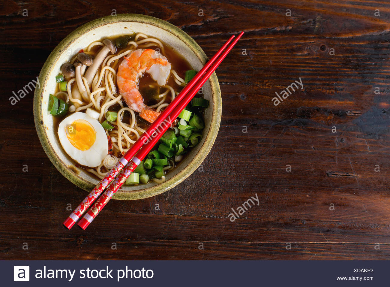 Ceramic bowl of asian ramen soup with shrimp, noodles, spring onion, sliced egg and mushrooms, served with red chopsticks over d - Stock Image