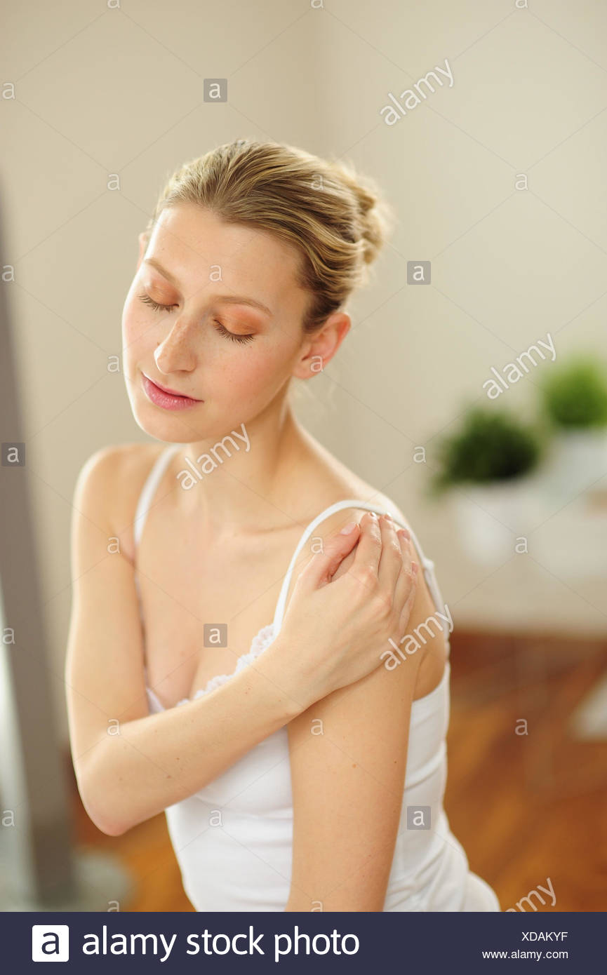 Young woman touches her shoulder, - Stock Image