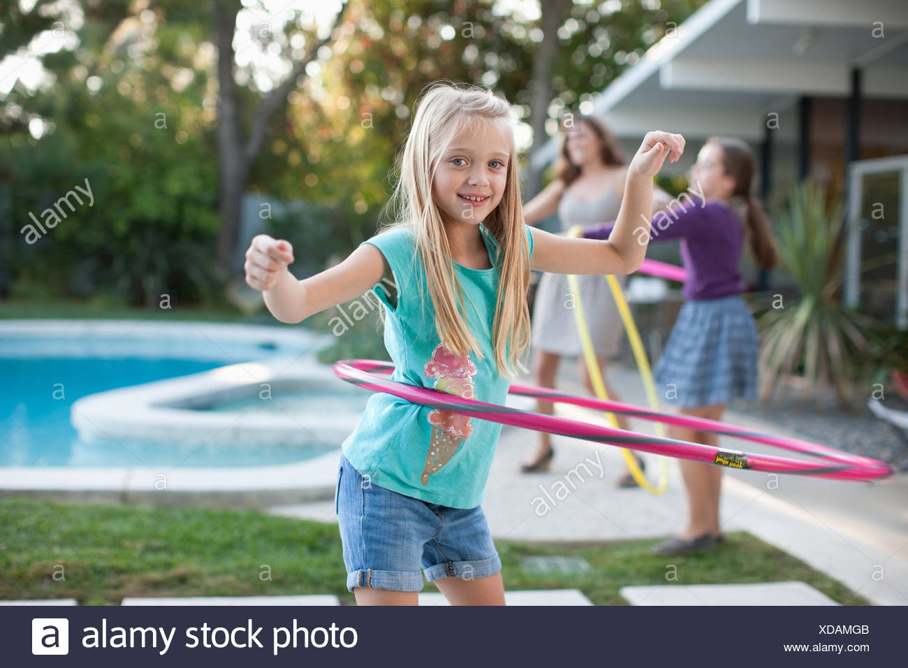 Mother and daughters hula hooping outdoors - Stock Image