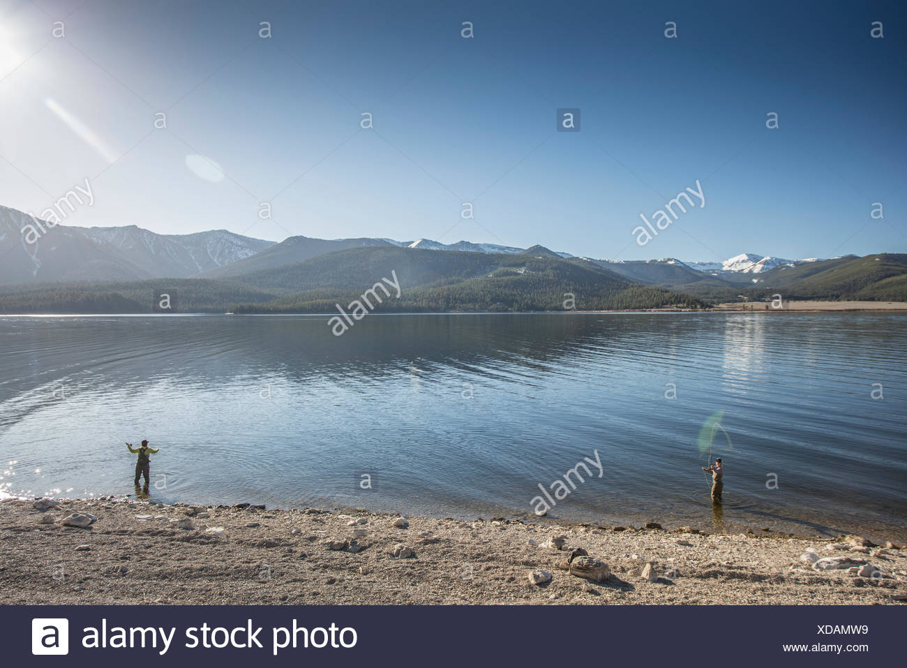 Two women cast from the shore while fly fishing on Montana's Hebgen Lake. - Stock Image