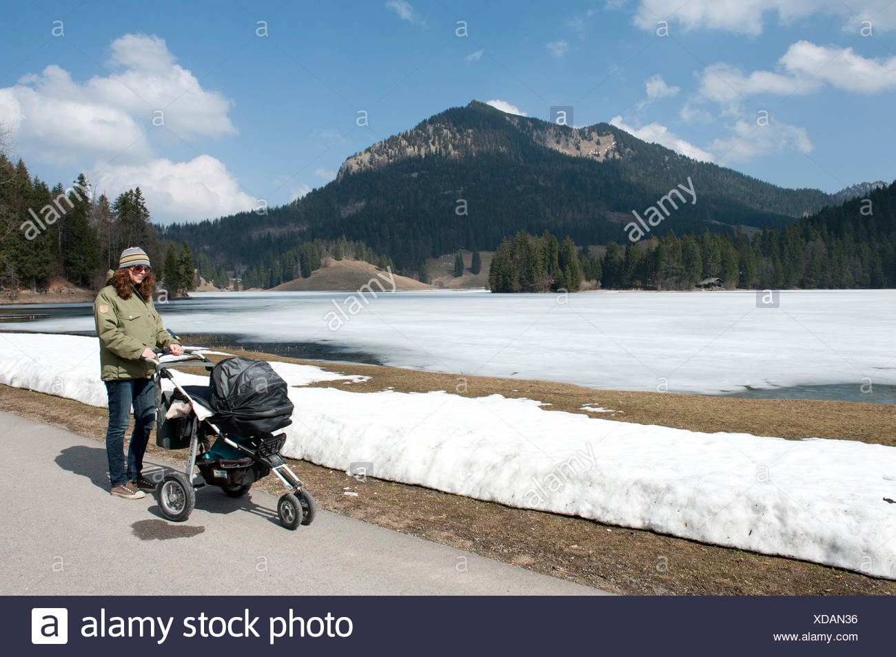 Mother with baby carriage walking on still frozen over Lake Spitzingsee in spring, 1084 m, snow patches - Stock Image
