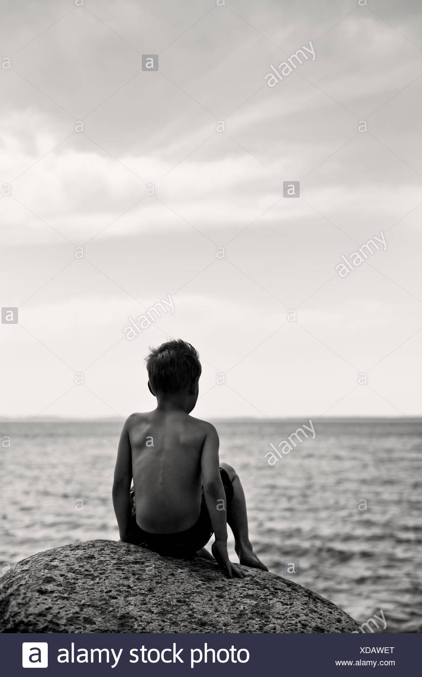 Boy sitting on rock by the sea stock image