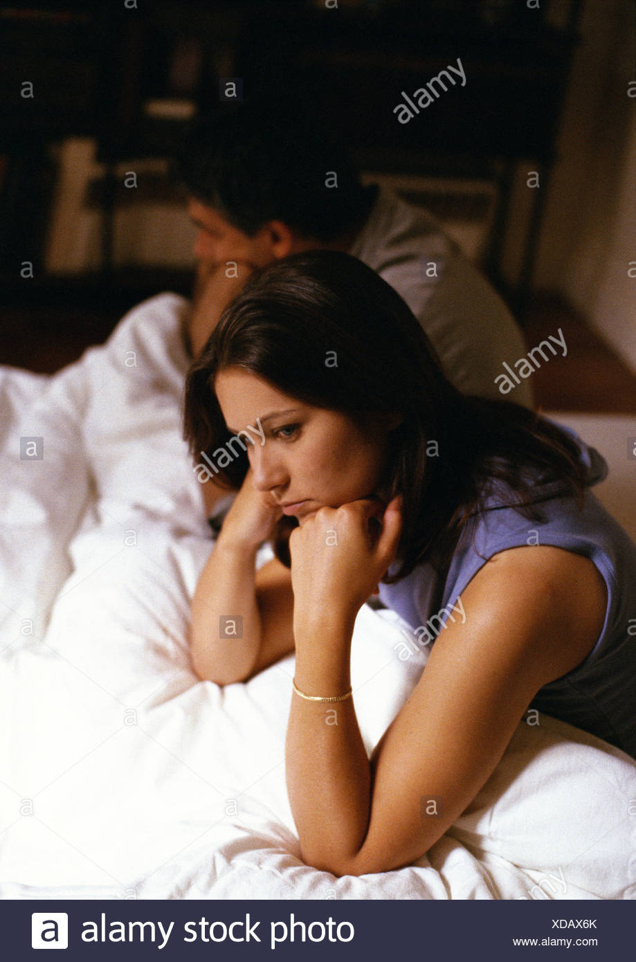 Couple sitting on bed, leaning on elbows, turned away from each other Stock Photo