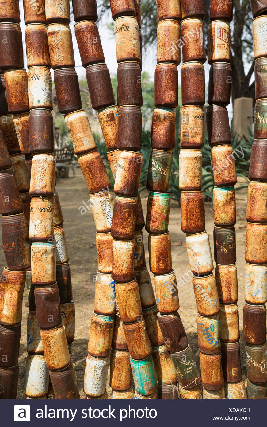 Fence made of old, rusty tins in the garden of a restaurant, recycling, Omaruru, Namibia - Stock Image